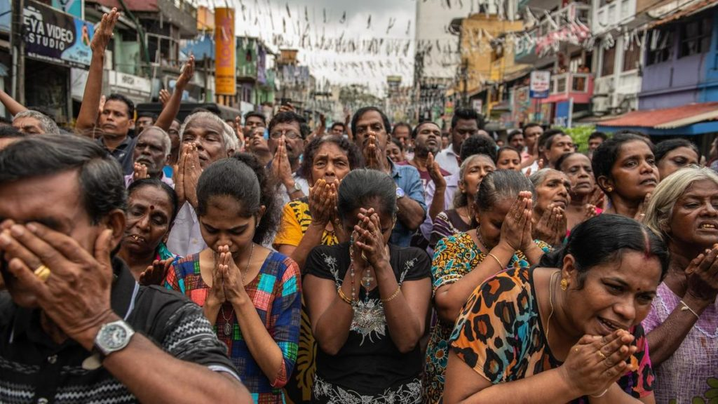 Sri Lankans pray in the street near St Anthony's Shrine a week after the attacks that killed over 250 people. Getty Images