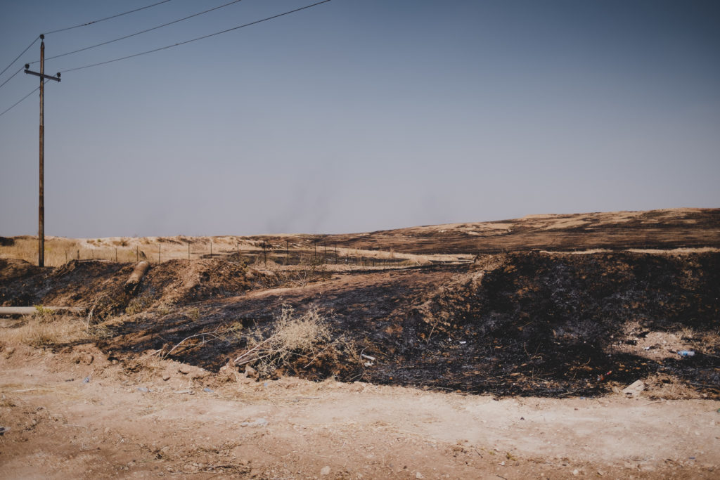 Fire destroyed the mass graves at the Hardan intersection where an estimated 250 Ezidis were executed on Auggust 3-4, 2014. (Photo: Kurdistan 24/Levi Clancy)
